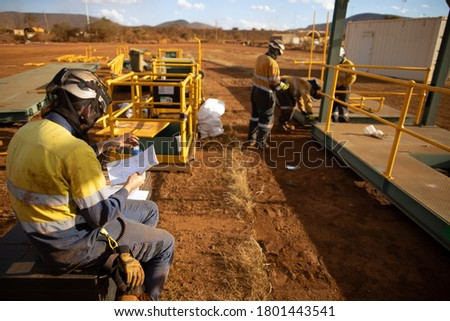 Construction site safety supervisor engineer wearing safety hard hat long sleeve hi-vis tape safety visible shirt  holding looking at defocused drawing building paperwork plan.  Royalty-Free Stock Photo #1801443541
