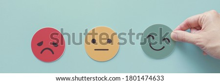 Hand choosing green happy smile face paper cut, feedback rating and positive customer review, experience, satisfaction survey ,mental health assessment, world mental health day concept Royalty-Free Stock Photo #1801474633