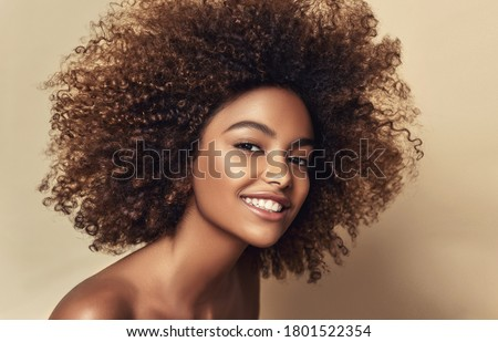 Beauty portrait of african american woman with clean healthy skin on beige background.  Smiling beautiful afro girl.Curly black hair   #1801522354