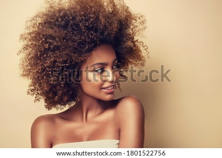 Beauty portrait of african american woman with clean healthy skin on beige background. Skin care and beauty concept. Smiling beautiful afro girl.Curly black hair  #1801522756
