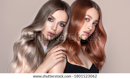 Beautiful women with curly hair.Two pretty girls with hair coloring in red and  shatush techniques. Stylish hairstyle curls done in a beauty salon. Fashion, cosmetics and makeup.