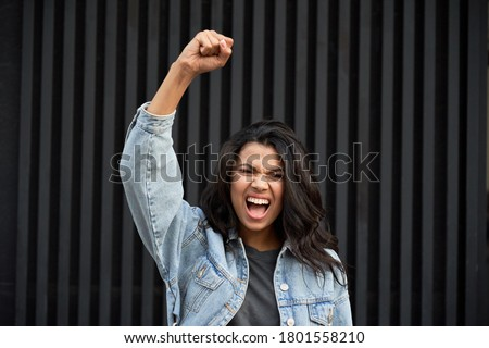 Angry brave African young woman standing on black background raising fist and screaming. Mixed race lady activist feminist leader fight for women rights, gender equality, empowerment protest concept. Royalty-Free Stock Photo #1801558210