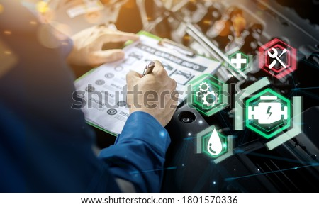 Mechanic engineer futuristic hologram icon repairing diagnosing checking motor vehicle car parts fixing issues problem broken engine, using clipboard pen man in professional uniform working in garage Royalty-Free Stock Photo #1801570336