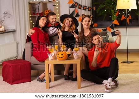 friendship, holiday and people concept - group of happy smiling friends in halloween costumes of vampire, devil, witch and cheetah taking selfie by smartphone at home party at night