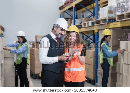 Female Inventory Manager Shows Digital Tablet Information to a Worker Holding Cardboard Box, They Talk and Do Work. In the Background Stock of Parcels with Products Ready for Shipment at warehouse