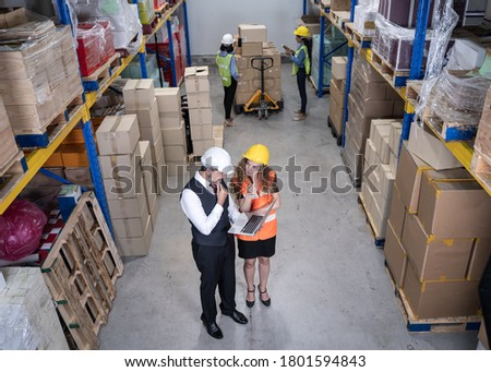 Inventory Manager Shows Digital laptop Information to a Worker Holding Cardboard Box, They Talk and Do Work. In the Background Stock of Parcels with Products Ready for Shipment at warehouse