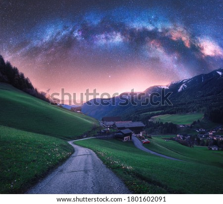 Arched Milky Way over the rural mountain road in summer in Italy. Beautiful night landscape with starry sky, milky way arch, winding road in mountain village, hills, green meadows and buildings. Space #1801602091