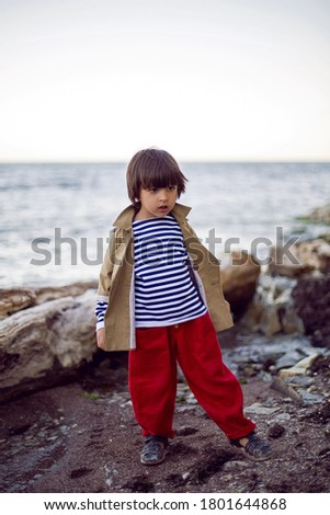 stylish boy sailor in a vest and red pants stands on the seashore in summer #1801644868