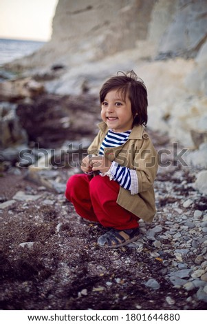 stylish boy sailor in a vest and red pants sit on the seashore in summer #1801644880