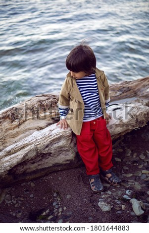 stylish boy sailor in a vest and red pants sit on the seashore in summer #1801644883