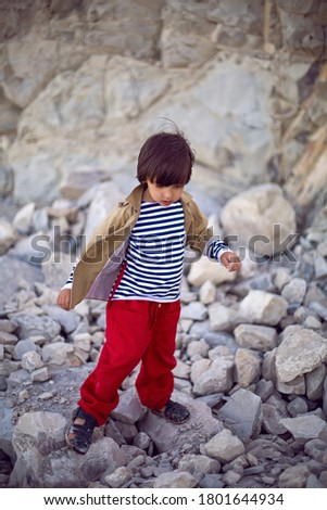 stylish boy sailor in a vest and red pants walk on the seashore in summer #1801644934