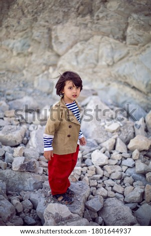 stylish boy sailor in a vest and red pants walk on the seashore in summer #1801644937