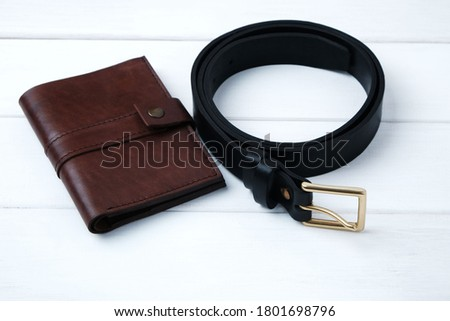 Wallet and belt made of genuine leather on white wooden background with copy space, handmade mens accessories. Royalty-Free Stock Photo #1801698796