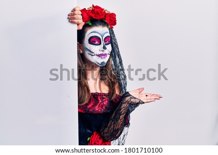 Young woman wearing day of the dead custome holding blank empty banner pointing aside with hands open palms showing copy space, presenting advertisement smiling excited happy