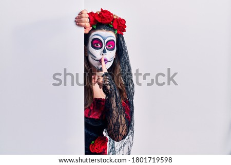 Young woman wearing day of the dead custome holding blank empty banner asking to be quiet with finger on lips. silence and secret concept.