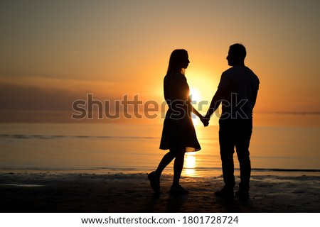 photo silhouette of a love couple. sunset, lake, romantic. portrait of a young woman and a man beach. Royalty-Free Stock Photo #1801728724