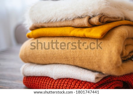 Bunch of knitted warm pastel color sweaters with different knitting patterns folded in stack on brown wooden table, grunged concrete wall background. Fall winter season knitwear. Close up, copy space