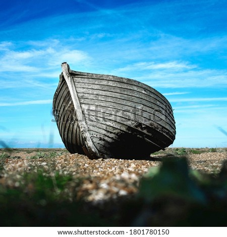 Wooden fishing boat on a sandy beach. Closeup pic of boat.