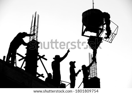 Construction workers are casting columns to build buildings using cranes. It is a black and white style picture. #1801809754