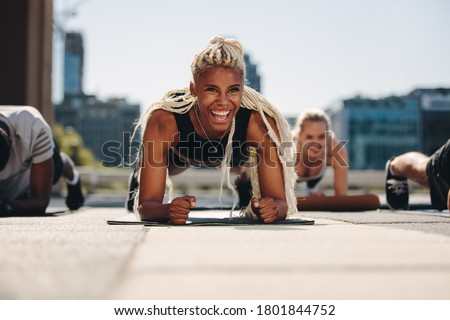 Group of young adults working out together outside in the city. Men and women holding a plank position and smiling. Royalty-Free Stock Photo #1801844752