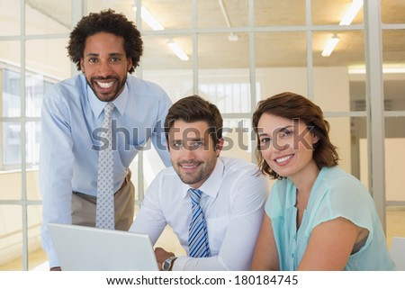 Portrait of three smiling young business people using laptop together at office desk #180184745