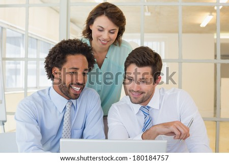Three smiling young business people using laptop together at office #180184757