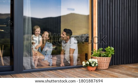 Young family with small daughter indoors, weekend away in container house in countryside. #1801887694