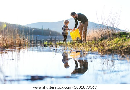 Father with small son collecting rubbish outdoors in nature, plogging concept. Royalty-Free Stock Photo #1801899367