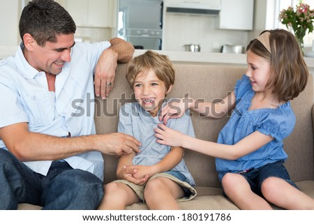 Father and daughter tickling boy sitting on sofa at home #180191786