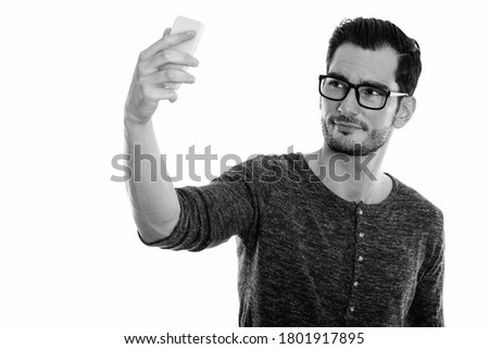 Studio shot of young handsome man taking selfie picture with mobile phone while wearing eyeglasses