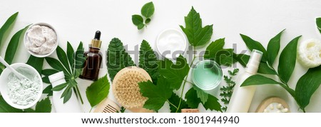Natural eco beauty. Cosmetic products and green leaves on white background, top view, banner. Natural organic skincare, spa, healthy lifestyle concept. Royalty-Free Stock Photo #1801944940