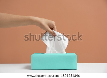 Woman taking paper tissue from box on light brown background, closeup Royalty-Free Stock Photo #1801951846
