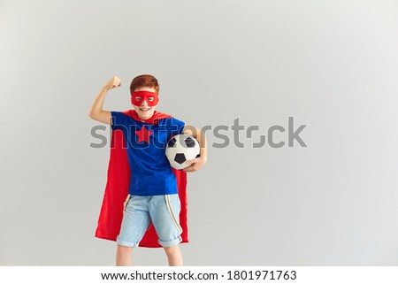 Smiling boy in superhero costume showing power and holding soccer ball in hand, copy space