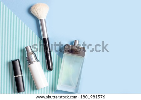 Women's cosmetics and accessories on a blue striped background: perfume, cream, lipstick, makeup brush. Fashion and Beauty Concept. #1801981576