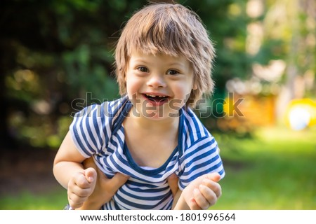 Portrait of Cute baby boy with Down syndrome playing in summer day on nature Royalty-Free Stock Photo #1801996564