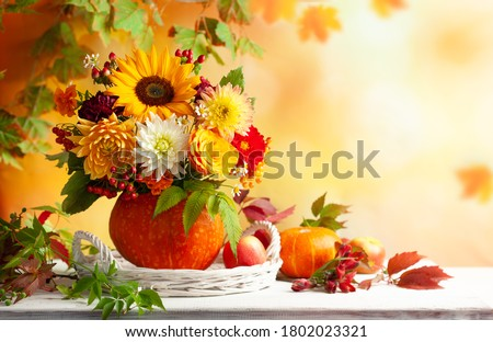 Autumn bouquet of beautiful flowers and berries in a pumpkin on wooden white table. Concept of autumn festive decoration for Thanksgiving day. #1802023321