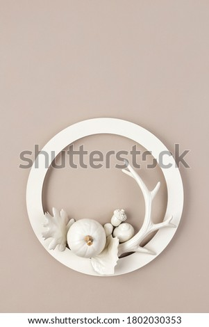 Modern Fall composition with white pumpkins, horn, acorn and dry leaf in circle frame. Halloween, Thanksgiving party concept. Festive fall design. Autumn composition. Creative Fall minimal concept.