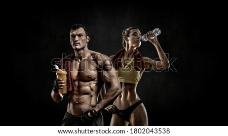 couple man with woman bodybuilders hold shaker with sportive nutrition - protein of shaker on black background with empty space for text. Gym concept #1802043538