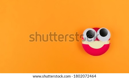 Cheese in form of little monster with eyes on orange backdrop. Halloween decor for party. Space for text. Food art