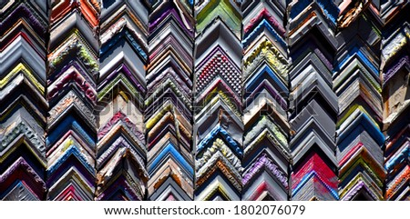 Background image of a wall composed of a miriad of picture frame corners.  They are stacked in rows.