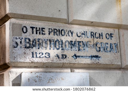 A vintage sign pointing people to the direction of the historic St. Bartholomew the Great church in the City of London, UK.