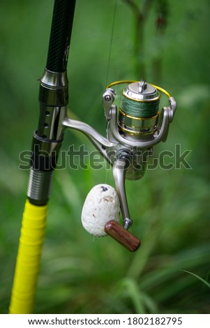 Against the background of green grass fishing rod for fishing. Against the background of green grass fishing rod for fishing