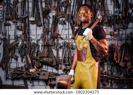 hammer industry small business concept.african american man dressed in historical clothing is hammering on the anvil. A blacksmith forges a metal product #1802204275