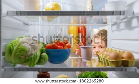 Cute Little Girl Opens Fridge Door, Looks inside Takes out Healthy Yogurt. Smart Little Child Eats Healthy. Shot from Inside the Fridge. Point of View POV Shot from Refrigerator full of Good Food Royalty-Free Stock Photo #1802265280
