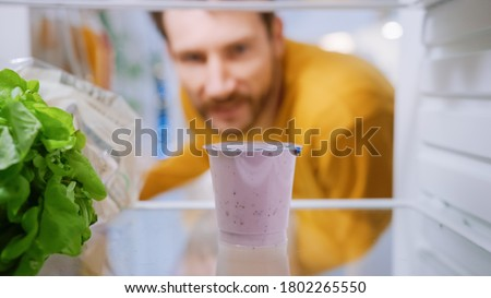 Camera Inside Kitchen Fridge: Handsome Man Opens Fridge Door, Thinks to Takes out Yogurt. Man Eating Healthy. Point of View POV Shot from Refrigerator full of Healthy Food Royalty-Free Stock Photo #1802265550