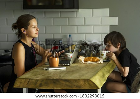 Young woman working at laptop with smartphone in hands. The boy is sitting at the table in front of mother, having breakfast and watching cartoons on his phone. Remote working and home office concept.