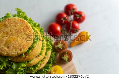 Fresh vegan chickpea burger (cutlets), tomatoes and lettuce. Home made with vegetables and chickpeas.The concept of healthy and vegetarian food. Place for text. Plant based food concept. Royalty-Free Stock Photo #1802296072