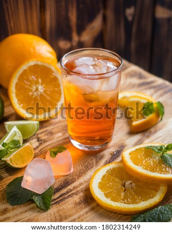 orange lemonade in a glass glass is on the table, on a wooden table orange lemonade, orange lemonade in a transparent glass orange slices restaurant menu glass with lemonade on the table #1802314249