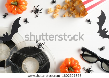Halloween party concept. Flat lay composition with halloween decorations, motion picture film reels, 3d glasses, popcorn, pumpkins, spiders, bats on white background. Watching horror movie