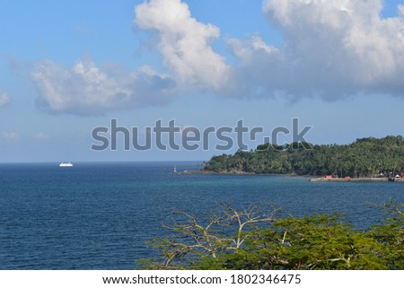 A scenic view with mountains, greens, ship, and amazing Indian Ocean. In the background we can see a boat and a island, increasing the beauty of this picture. It is a perfect pic to set as wallpaper.
